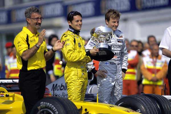 Kimi Räikkönen hands over the Brazilian Grand Prix trophy for 1st position to Giancarlo Fisichella, after the results of the race were amended. Regulations regarding a race being abandoned following a red flag were incorrectly applied at the time. Eddie Jordan is also present.