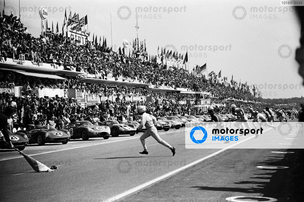 Drivers sprint to their cars as the starter drops the flag to signal the start of the race.