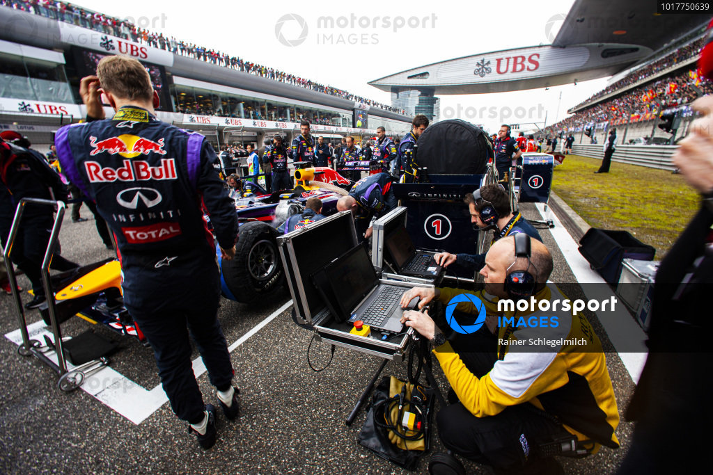 Renault and Red Bull engineers at work beside Sebastian Vettel, who is beside Red Bull RB10 Renault.