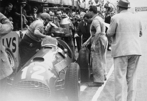 1951 British Grand Prix. Silverstone, Great Britain. 14 July 1951. Jose Froilan Gonzalez, (Ferrari 375), 1st position. Teammate Alberto Ascari looks on as Gonzalez's winning car makes a pit stop. This was Ferrari's first GP victory. Ref-51/37 #31. World Copyright - LAT Photographic