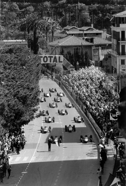 1964 Monaco Grand Prix.Monte Carlo, Monaco. 7-10 May 1964.Jack Brabham (#5 Brabham BT7-Climax) and Jim Clark (#12 Lotus 25-Climax) on the front row of the grid before the start. John Surtees (#21 Ferrari 158), Graham Hill (#8 BRM P261), Peter Arundell (#11 Lotus 25-Climax) and Dan Gurney (#6 Brabham BT7-Climax) line up behind.World Copyright: LAT PhotographicRef: Autosport b&w print