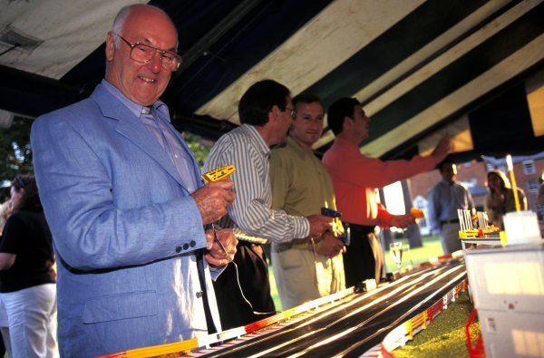 ITV Formula One commentator Murray Walker (GBR), pundit Simon Taylor (GBR), Presenter Jim Rosenthal (GBR) and Pit Reporter James Allen (GBR) play with a scalextric. Formula One World Championship, Rd9, British Grand Prix, Silverstone, England, 13 July 1997.
