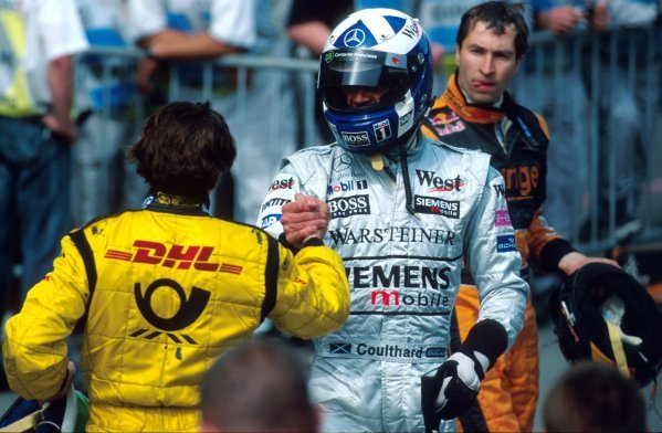 David Coulthard (GBR) McLaren and Giancarlo Fisichella (ITA) Jordan congratulate each other in Parc Ferme after the race.Formula One World Championship, Rd6, Austrian Grand Prix, A1-Ring, Austria. 12 May 2002.BEST IMAGE