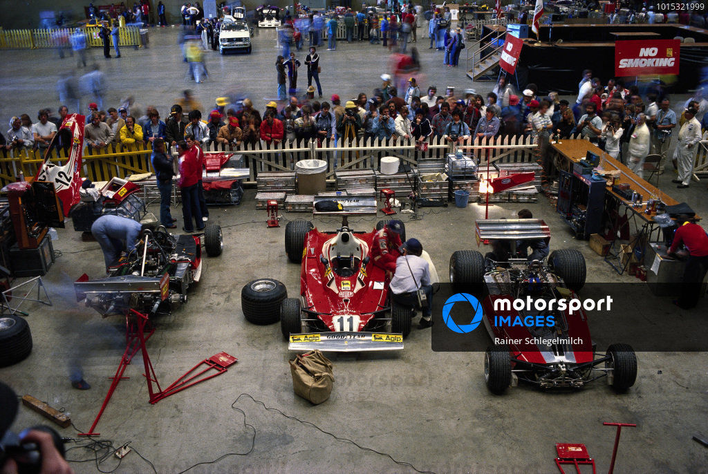 Fans watch as mechanics work on Ferrari 312T2s in the paddock.