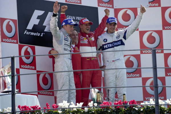 Podium group photo: Kimi Räikkönen, 2nd position, Ferrari team boss Jean Todt, winner Michael Schumacher and Robert Kubica, 3rd position.