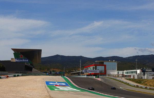 Esteban Ocon, Alpine A521, passes as Nicholas Latifi, Williams FW43B, enters the pits