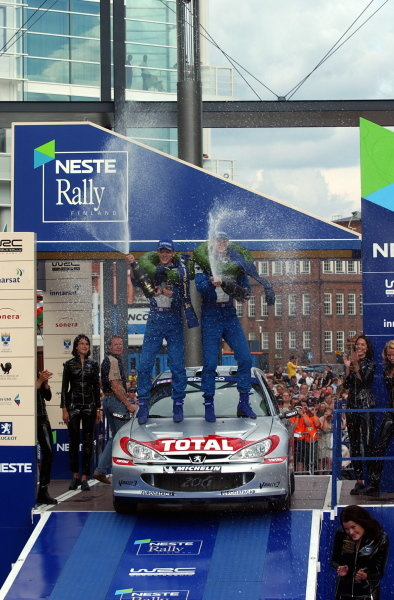 Rally winner Marcus Gronholm (FIN) and team mate Timo Rautiainen (FIN) Peugeot 206 WRC spray champagne.