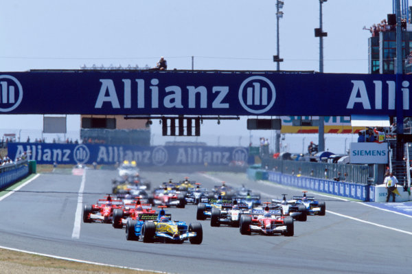 2005 French Grand Prix. Magny-Cours, France. 1st - 3rd July 2005 Fernando Alonso, Renault R25 leads the field going into turn 1 on the opening lap of the race. Action. World Copyright: Lorenzo Bellanca/LAT Photographic Ref: 35mm Image A01
