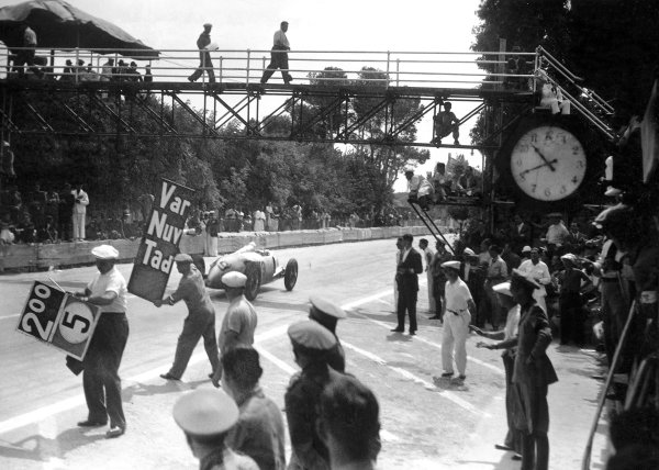 1935 Coppa Acerbo. Pescara, Italy. 15th August 1935. Achille Varzi (Auto Union B) learns just who is behind him as he passes the pits. World Copyright: Robert Fellowes/LAT Photographic Ref: 35CA13
