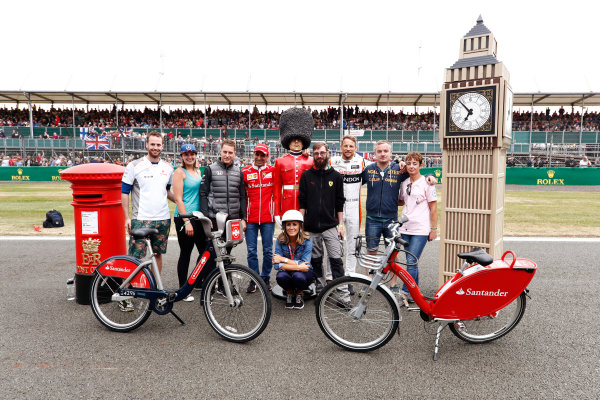Silverstone, Northamptonshire, UK.  Thursday 13 July 2017. Stoffel Vandoorne, McLaren,Marc Gene of Ferrari and Jenson Button, McLaren, pose with guests and Sky presenter Natalie Pinkham. World Copyright: Glenn Dunbar/LAT Images  ref: Digital Image _X4I2736