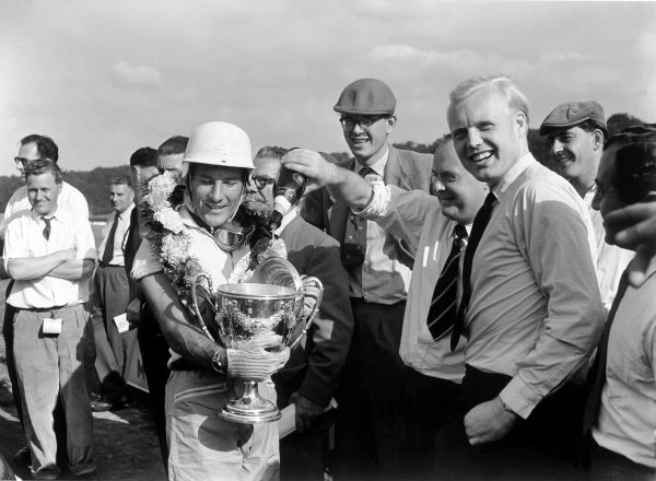 Brands Hatch, England. 30th August 1958.Stirling Moss (Cooper-Climax), 1st position, with trophy and champagne, presented by Mike Hawthorn, portrait.World Copyright: LAT PhotographicRef: Autocar Glass Plate C53354.
