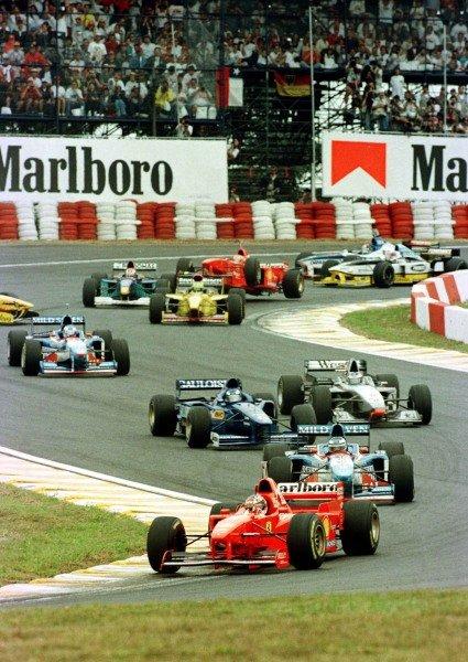 "1997 Brazilian Grand Prix.Interlagos, Sao Paulo, Brazil.28-30 March 1997.Michael Schumacher (Ferrari F310B) leads at Senna's ""s"" on the first start while Jacques Villeneuve (Williams FW19 Renault) crashes with Giancarlo Fisichella (Jordan 197 Peugeot) and Eddie Irvine (Ferrari F310B, airborn).World Copyright - LAT Photographic"