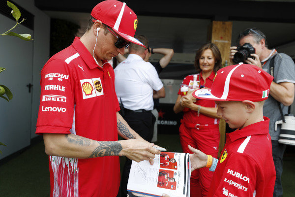 Kimi Raikkonen, Ferrari, signs an autograph for a young fan.