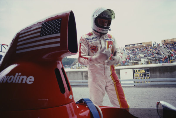 Mario Andretti stands next to his Parnelli VPJ4B Ford in the pits.