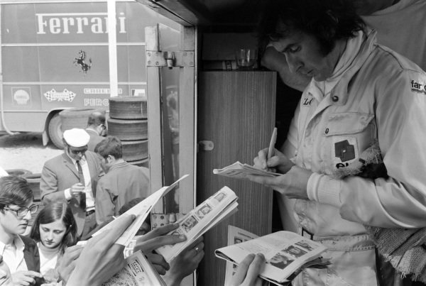 Jackie Stewart signs autographs for fans.
