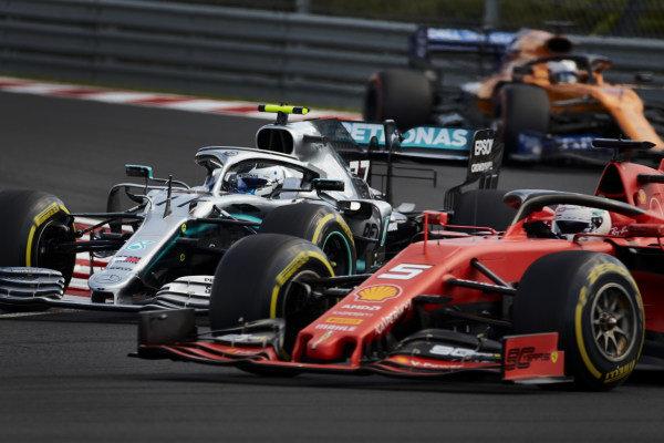 Sebastian Vettel, Ferrari SF90, leads Valtteri Bottas, Mercedes AMG W10, and Carlos Sainz Jr., McLaren MCL34