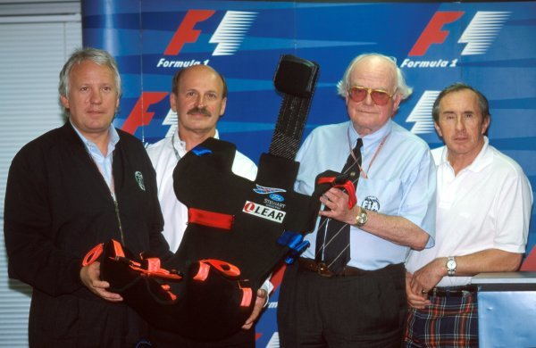 The new 1999 extractable safety seat, designed by LEAR, was on display in Japan with (L to R): Charlie Whiting (GBR) FIA Safety Delegate, a LEAR representative, Doctor Syd Watkins (GBR) FIA Doctor and former World Champion and safety campaigner Jackie Stewart (GBR) Stewart Team Principal. Formula One World Championship, Japanese GP, Rd 16, Suzuka, Japan, 1 November 1998.