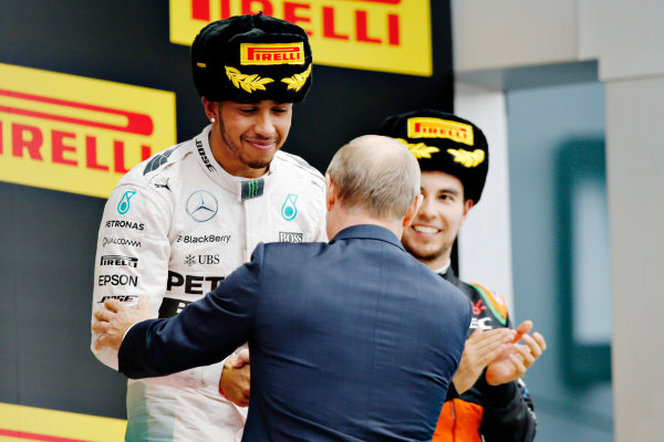 Sochi Autodrom, Sochi, Russia. Sunday 11 October 2015. Lewis Hamilton, Mercedes AMG is congratulated by Russian President Vladimir Putin on the podium. World Copyright: Alastair Staley/LAT Photographic. ref: Digital Image _R6T2438
