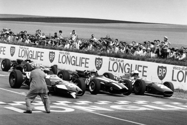 1966 French Grand Prix. Reims, France. 1-3 July 1966. (L-R) Lorenzo Bandini (Ferrari 312), John Surtees (Cooper T81 Maserati) and Michael Parkes (Ferrari 312) on the front row of the grid at the start. Parkes finished in 2nd position. A Race Through Time exhibition number 89. World Copyright - LAT Photographic Ref: 35354