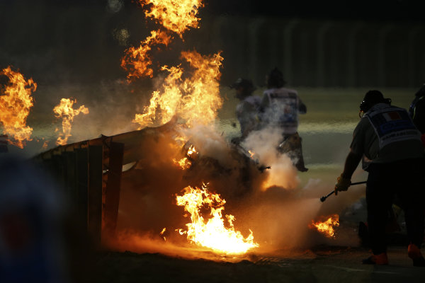 The wreckage of the Romain Grosjean Haas VF-20 after a horrific accident on the opening lap of the Bahrtain Grand Prix. The car punctured a hole through the armco barrier and exploded into flames, Marshals attend the fire