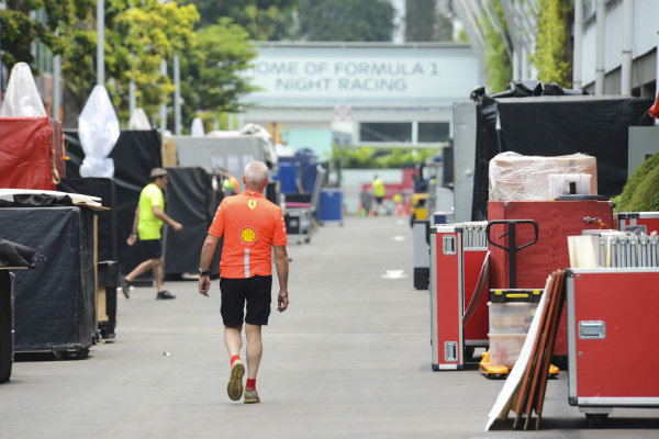 A Ferrari team member surrounded by freight in the paddock