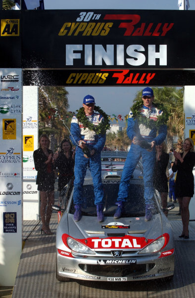 World Rally Championship, Cyprus Rally, April 18-21, 2002.Marcus Gronholm (R) and Timo Rautiainen (L) spray the victory champagne on the podium.Photo: Ralph Hardwick/LAT