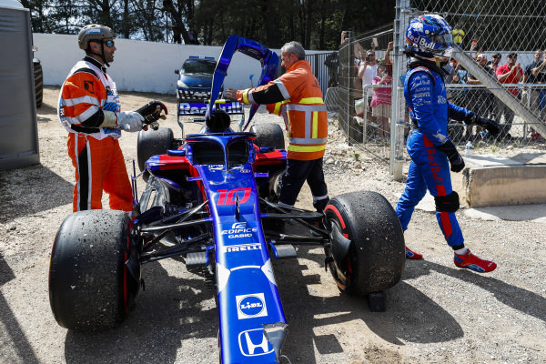 Marshals remove the damaged car of Pierre Gasly, Toro Rosso STR13 Honda, as he walks away.