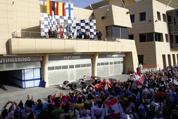 Fernando Alonso celebrates victory on the podium with Michael Schumacher, 2nd position, and Kimi Räikkönen, 3rd position as teams and fans celebrate below.