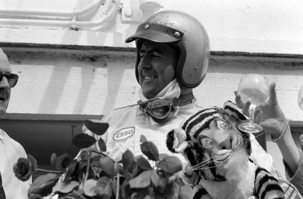 Race winner Jack Brabham celebrates on the podium with flowers and the Esso tiger mascot.
