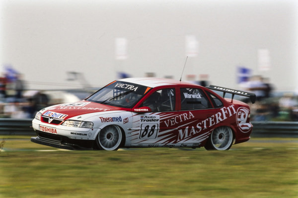 Derek Warwick, Vauxhall Sport, Vauxhall Vectra, goes up on two wheels over a kerb.