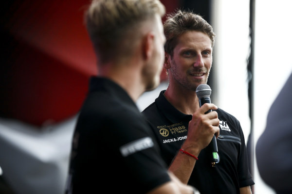 Kevin Magnussen, Haas F1, and Romain Grosjean, Haas F1, on stage