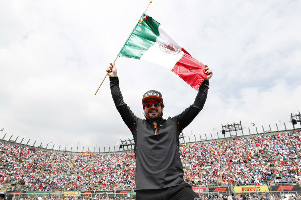 Fernando Alonso, McLaren, celebrates with a Mexican flag ahead of the race