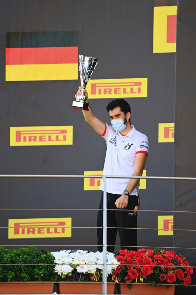A Hitech team member celebrates with his trophy on the podium