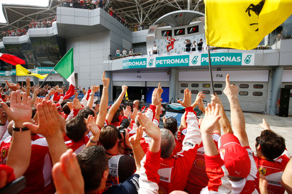 Sepang International Circuit, Sepang, Kuala Lumpur, Malaysia. Sunday 29 March 2015. Sebastian Vettel, Ferrari, 1st Position, arrives on the podium to the cheers of his Ferrari team. World Copyright: Andrew Hone/LAT Photographic. ref: Digital Image _ONY1015