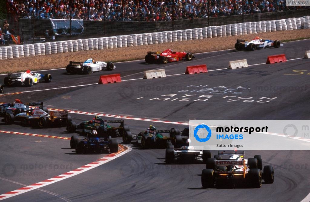 The field make their way through a temporary chicane inserted to tame the legendary Eau Rouge. Thankfully safety improvements allowed the corner to return to its former glory the following season. The chicane contains a personal tribute from a fan to the late Ayrton Senna (BRA). Belgian Grand Prix, Spa-Francorchamps, Belgium, 28 August 1994.