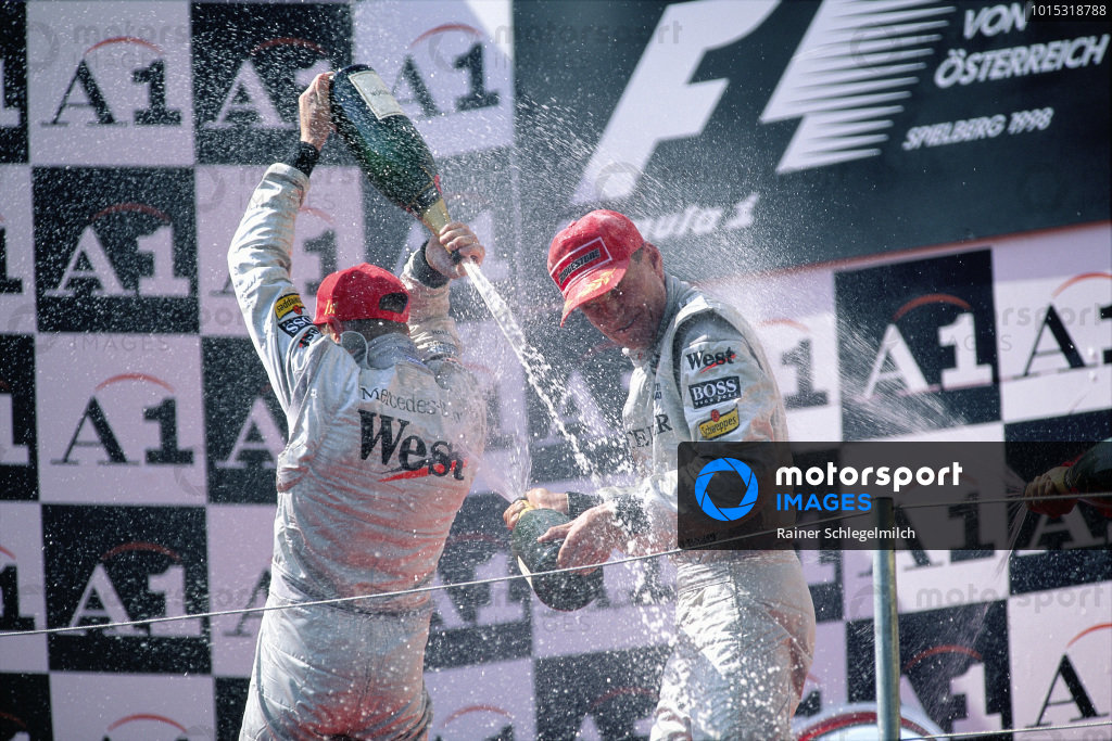 Mika Hakkinen, 1st position, and David Coulthard, 2nd position, celebrate on the podium.