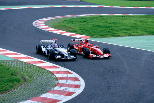 2004 Belgian Grand Prix.Spa Francorchamps, Belgium. 27th - 29th August.Juan Pablo Montoya, WilliamsF1 BMW FW26 overtakes Michael Schumacher, Ferrari F2004 going into the bus stop. Action. World Copyright:LAT PhotographicRef:35mm Image A09