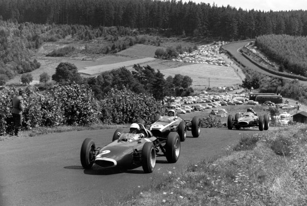 1963 German Grand Prix.  Nurburgring, Germany. 4 August 1963.  Richie Ginther, BRM P57, 3rd position, leads Bruce McLaren, Cooper T66-Climax, retired, and Graham Hill, BRM P57, retired, at Flugplatz.  World Copyright: LAT PhotographicRef: L63/242/13