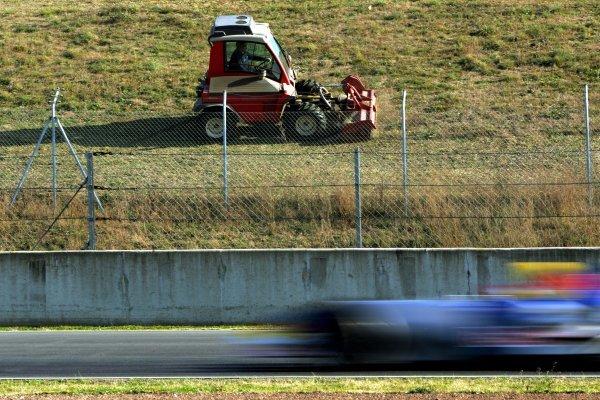 Vitantonio Liuzzi (ITA) Red Bull Racing RB01 races past a lawn mower.Formula One Testing, Barcelona, Spain, 18 January 2005.DIGITAL IMAGE