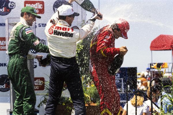 Alex Zanardi, 1st position, celebrates on the podium with Michael Andretti, 2nd position, and Dario Franchitti, 3rd position.