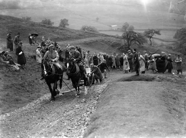 Horses and spectators assist a car up an incline.