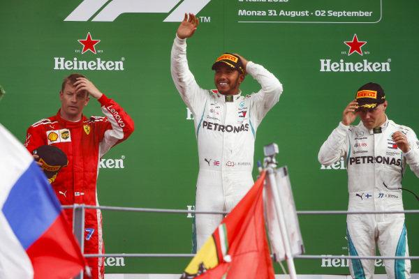 Kimi Raikkonen, Ferrari, 2nd position, Lewis Hamilton, Mercedes AMG F1, 1st position, and Valtteri Bottas, Mercedes AMG F1, 3rd position, celebrate on the podium.