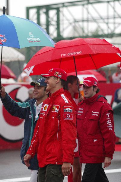 2004 Italian Grand Prix - Sunday Race,Monza, Italy. 12th September 2004 Michael Schumacher, Ferrari F2004, Felipe Massa, Sauber Petronas C23, and Ricardo Zonta, Toyota TF104, shelter from the rain.World Copyright: Steve Etherington/LAT Photographic ref: Digital Image Only