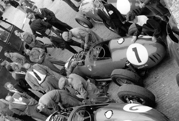 1959 Dutch Grand Prix.Zandvoort, Holland. 31 May 1959.Carlo Chiti (glasses, centre) overseas mechanics working on the car of Jean Behra, Ferrari Dino 246, 5th position, in the paddock.World Copyright: LAT Photographic