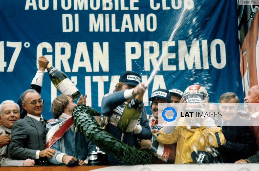 Monza, Italy. 10 - 12 September 1976. Ronnie Peterson (March 761-Ford), 1st position, celebrates with Clay Regazzoni (Ferrari 312T2), 2nd position and Jacques Laffite (Ligier JS5-Matra), 3rd position, on the podium, portrait.  World Copyright: LAT Photographic. Ref:  76ITA01.
