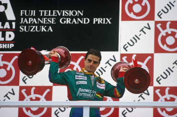 Suzuka, Japan. 20-22 October 1989. Alessandro Nannini (Benetton B189 Ford) celebrates 1st position on the podium. Portrait. Trophy. Ref: 89 JAP 04. World Copyright - LAT Photographic