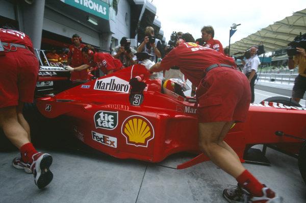 Sepang, Kuala Lumpur, Malaysia. 15-17 October 1999. Mechanics push Michael Schumacher (Ferrari F399) back into the garage. Ref: 99MAL16. World Copyright - LAT Photographic