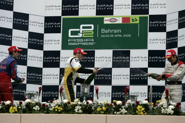 2008 GP2 Asia Series. Saturday Race.Bahrain International Circuit. Sakhir, Bahrain. 5th April. Romain Grosjean (FRA, ART Grand Prix) celebrates victory on the podium with Sebastien Buemi (SUI, Trust Team Arden) and Kamui Kobayashi (JPN, Dams). World Copyright: Alastair Staley/GP2 Series Media Service. Service ref:__MG_3594 jpg
