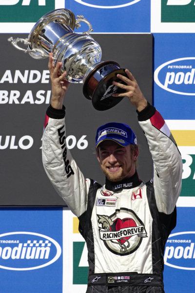 Jenson Button raises his 3rd place trophy on the podium.