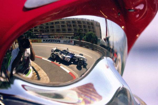 Juan Pablo Montoya, Williams FW25 BMW, rounding Loews Hairpin, reflected in a fire marshals visor.